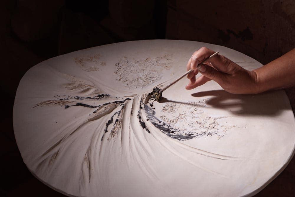 main qui peint de la céramique